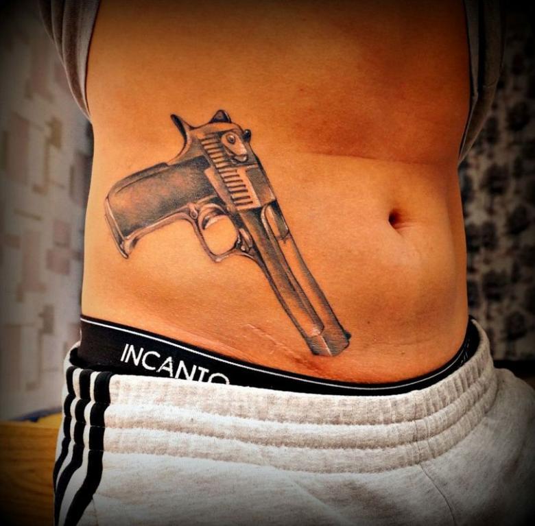 Тату на пояснице пистолеты фото